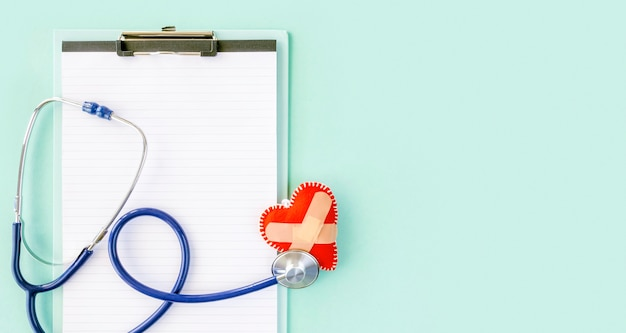 Vista dall'alto della forma di cuore danneggiato con stetoscopio e blocco note Foto Gratuite