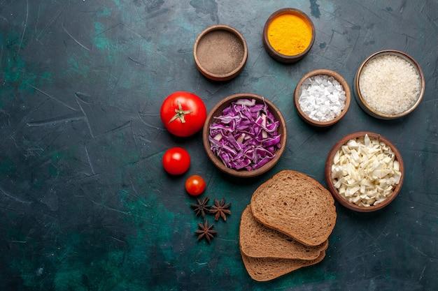 ダークブルーの机に調味料とスライスしたキャベツを添えたトップビューのダークパンのパン野菜料理食事皿パンの色 無料写真