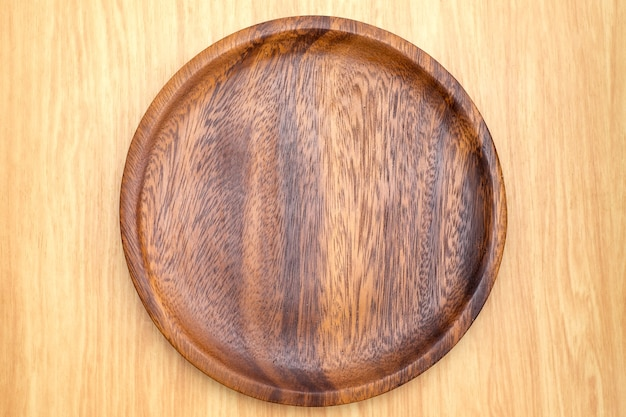 Top view of dark brown wooden plate on light wood counter Premium Photo