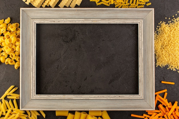A top view dark photo frame along with different formed yellow raw pasta isolated on the dark Free Photo