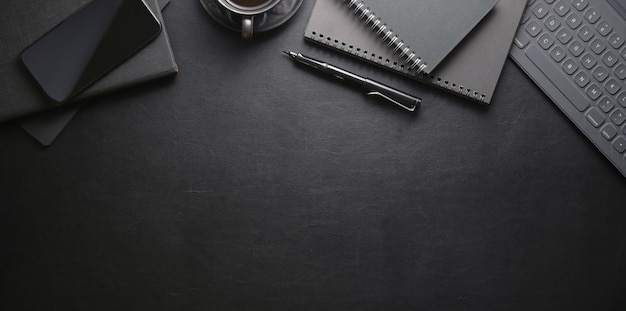 Top view of dark stylish workplace with smartphone and office supplies Premium Photo