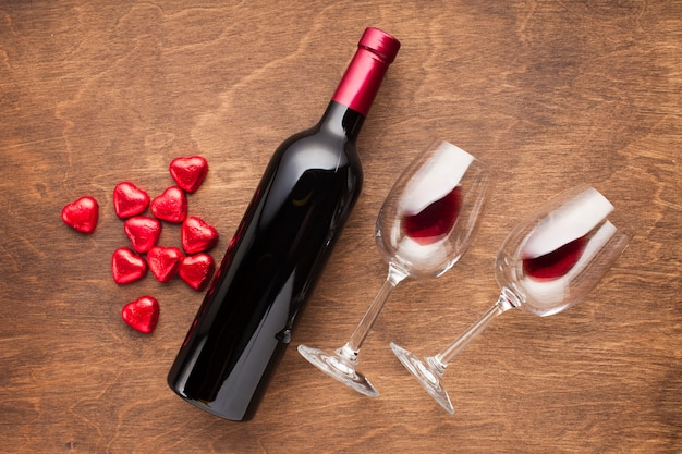 Top view decoration with heart shaped candies and wine Free Photo
