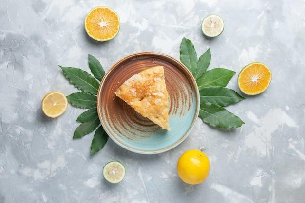 Vista dall'alto deliziosa torta di mele all'interno del piatto sulla scrivania leggera torta torta biscotto zucchero dolce cuocere Foto Gratuite
