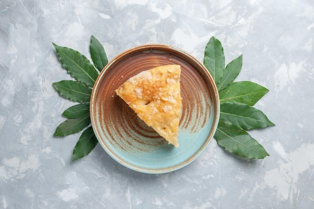 Vista dall'alto deliziosa torta di mele all'interno del piatto su scrivania bianca torta torta biscotto zucchero dolce cuocere Foto Gratuite