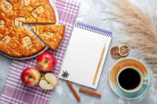 Vista dall'alto deliziosa torta di mele all'interno del piatto con blocco note di mele e tazza di tè su sfondo chiaro torta biscotto torta dolce Foto Gratuite