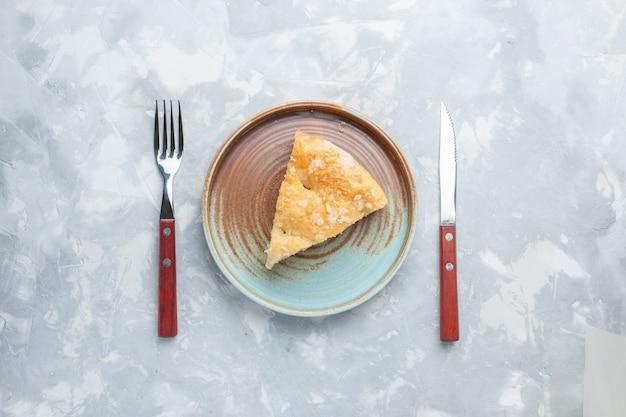 Vista dall'alto deliziosa torta di mele affettata all'interno della piastra sulla scrivania bianca torta torta di zucchero dolce cuocere il biscotto Foto Gratuite