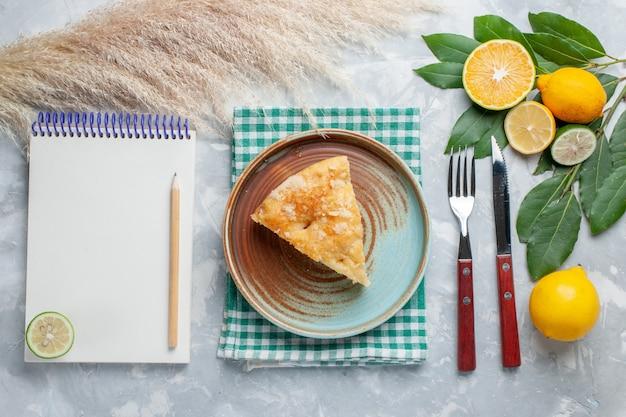 Vista dall'alto deliziosa torta di mele affettata all'interno del piatto con limoni sul biscotto dolce torta torta scrivania leggera Foto Gratuite