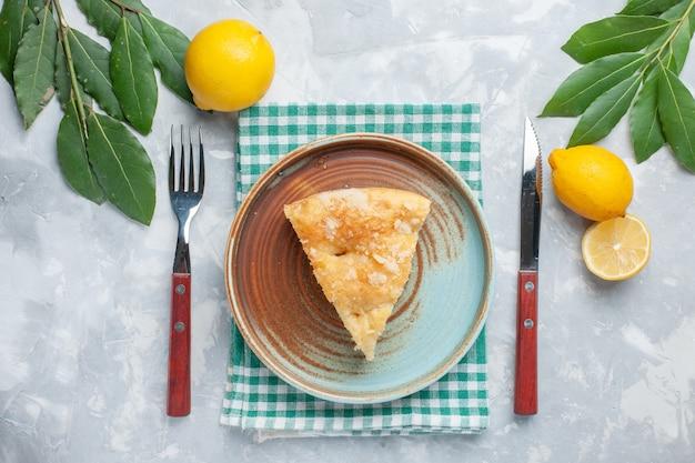 Vista dall'alto deliziosa torta di mele affettata all'interno del piatto con limoni sulla scrivania bianca torta torta cuocere il biscotto Foto Gratuite
