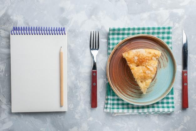 Vista dall'alto deliziosa torta di mele affettata all'interno del piatto con blocco note sulla scrivania bianca torta torta zucchero dolce cuocere il biscotto Foto Gratuite