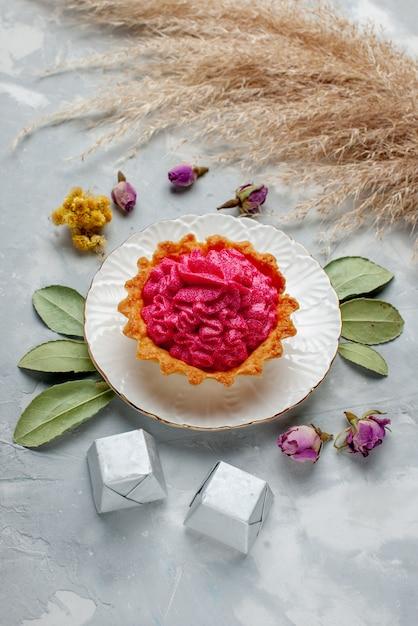Vista dall'alto di una deliziosa torta al forno con crema rosa e cioccolatini sulla luce, tè alla crema dolce da forno Foto Gratuite