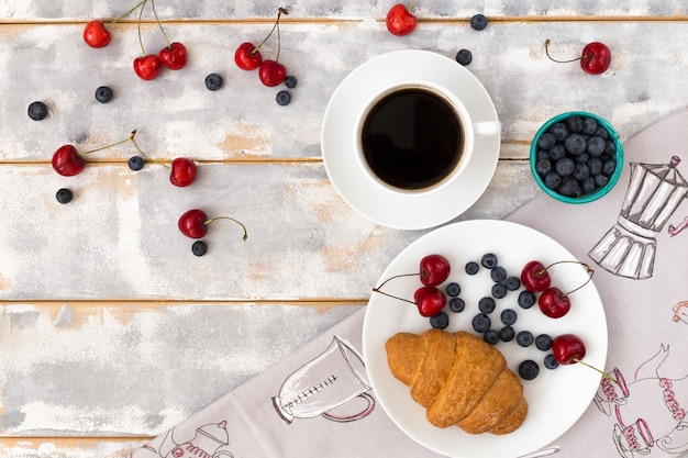 Top view of a delicious breakfast with croissants, coffee and blueberries and cherries on the table Premium Photo