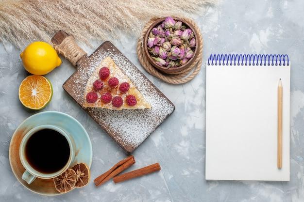 ライトデスクケーキビスケットスイートシュガーベイクにお茶とレモンのメモ帳を添えたトップビューのおいしいケーキスライス 無料写真