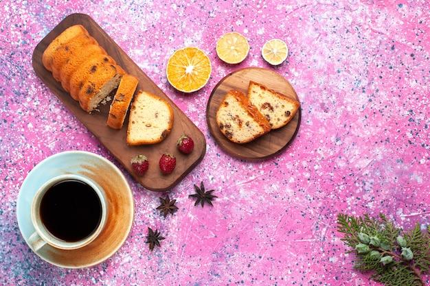 Vista dall'alto deliziosa torta dolce e gustosa a fette con una tazza di tè sulla scrivania rosa. Foto Gratuite