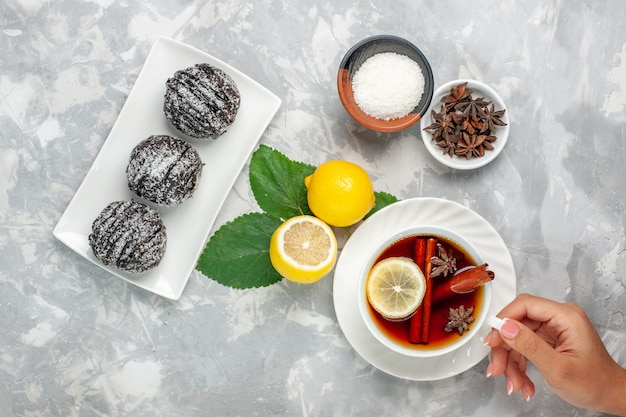 Top view delicious chocolate cakes little round formed with lemon and cup of tea on white surface fruits cake biscuit sweet sugar bake cookie Free Photo