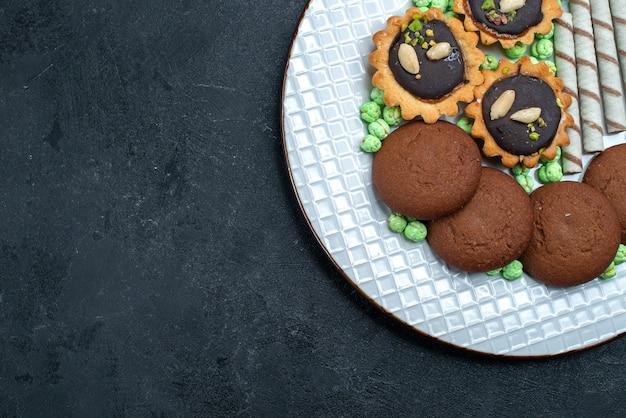 トップビュー灰色の背景にキャンディーとおいしいクッキービスケットシュガーベイクケーキパイティークッキー 無料写真