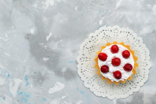トップビューグレーの表面にクリームと赤いフルーツのおいしいクリーミーなケーキビスケット甘いケーキシュガーフルーツ 無料写真