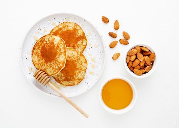 Вид сверху вкусные блины с медом и миндалем Бесплатные Фотографии