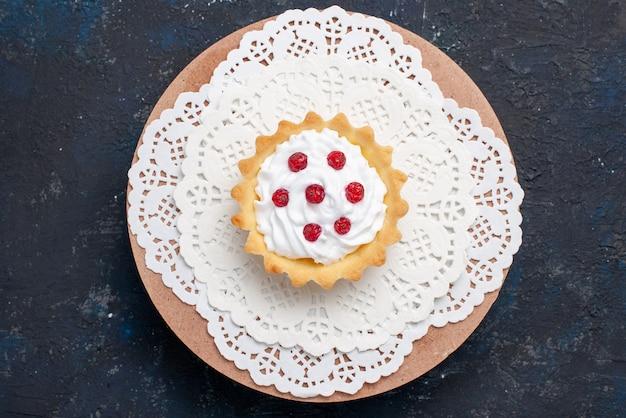 トップビューダークブルーの表面のケーキフルーツビスケットにクリームと赤のフルーツとおいしいdケーキ 無料写真