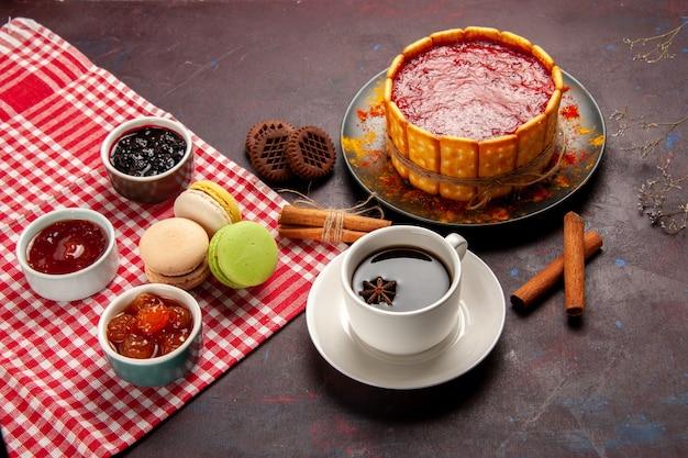 Vista dall'alto una deliziosa torta da dessert con una tazza di caffè e marmellate di frutta sulla superficie scura del biscotto di zucchero Foto Gratuite