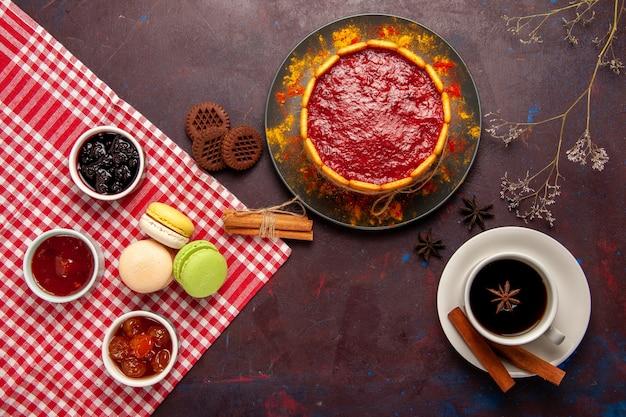 トップビューダークデスクにコーヒーとフルーツジャムを添えたおいしいデザートケーキビスケットシュガークッキーケーキデザートスイート 無料写真