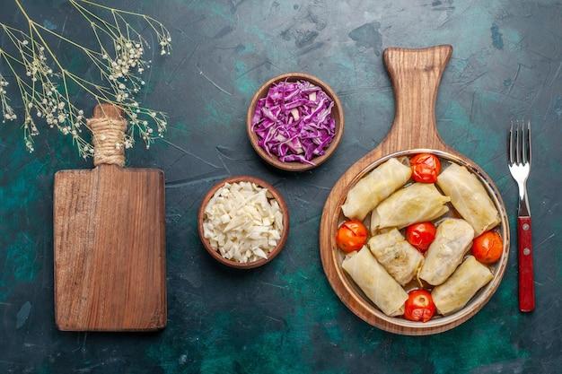 上面図紺色の背景にキャベツとトマトを巻いたおいしいドルマ肉料理夕食野菜料理 無料写真