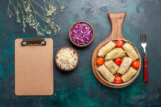 Vista dall'alto delizioso dolma farina di carne arrotolata con cavolo e pomodori sulla scrivania blu scuro carne cibo cena verdure piatto di cottura Foto Gratuite