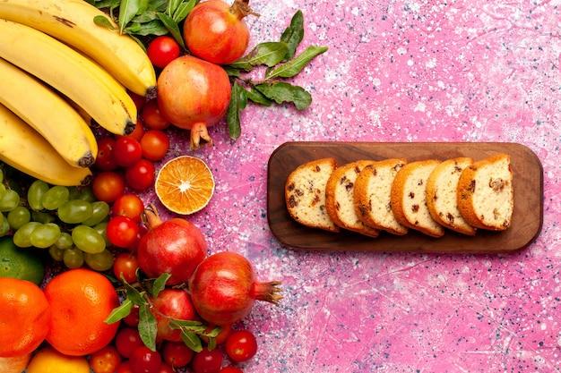 淡いピンクの机の上にスライスしたケーキとトップビューのおいしい果物の組成物 無料写真