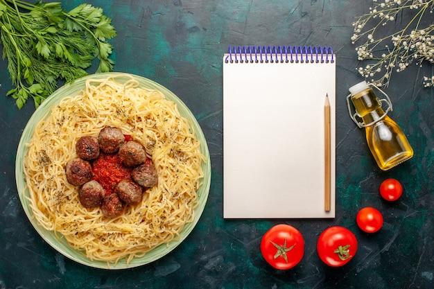 トップビューダークブルーの背景にミートボールとトマトソースのおいしいイタリアンパスタ生地パスタ料理肉ディナーフードイタリア 無料写真