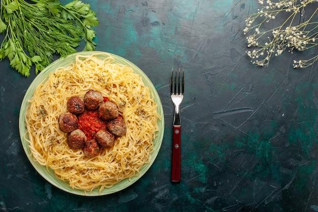 トップビューダークブルーの背景にミートボールとトマトソースのおいしいイタリアンパスタ生地パスタ料理ディナーフードイタリア 無料写真