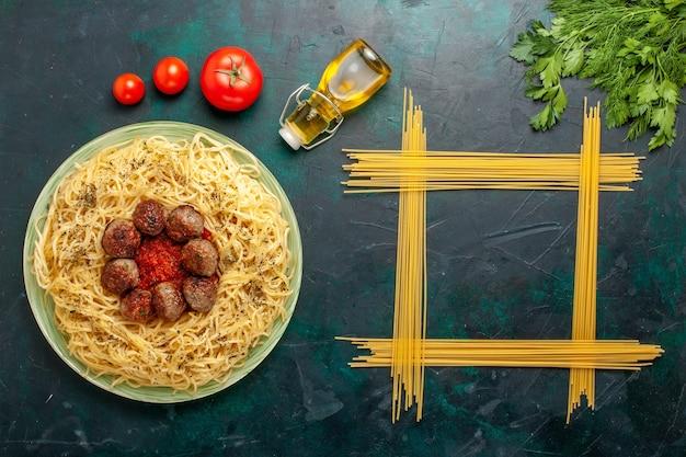 トップビューダークブルーの背景にミートボールとトマトソースのおいしいイタリアンパスタ生地パスタ食事料理ディナーフードイタリア 無料写真