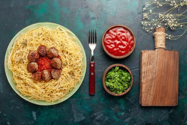 トップビューダークブルーの背景にミートボールとトマトソースのおいしいイタリアンパスタ生地パスタフードミールディッシュディナー 無料写真
