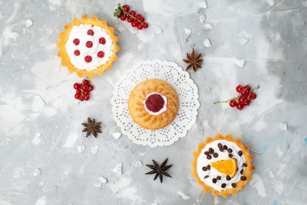 Вид сверху вкусные маленькие пирожные со сливками и красными фруктами на светлом столе, сладкое Бесплатные Фотографии