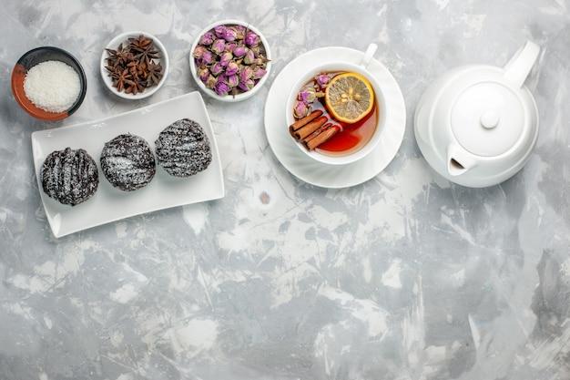 トップビューライトホワイトの背景にアイシングとお茶のおいしい小さなケーキティービスケットケーキ焼き砂糖甘いパイクッキー 無料写真