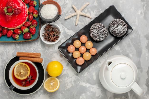 上面図美味しそうなケーキ小さなパイとお茶のクッキーと新鮮なイチゴの明るい白の表面のケーキビスケットクッキークリームスイート 無料写真