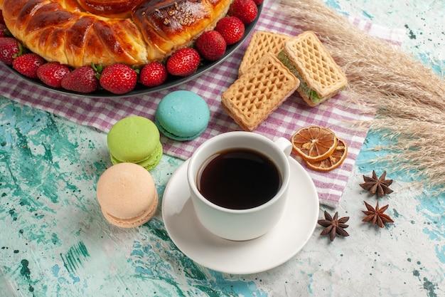 Torta deliziosa vista dall'alto con una tazza di tè e fragole rosse fresche sulla superficie blu Foto Gratuite