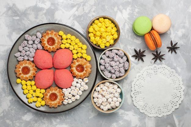 トップビュー白い机の上にキャンディーとクッキーとおいしいピンクのケーキ甘いケーキビスケットティーパイクッキー 無料写真