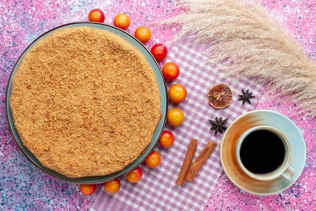 Вид сверху восхитительный круглый торт внутри тарелки с облицованными черносливом и чаем на розовом столе торт пирог бисквит сладкая выпечка сахар Бесплатные Фотографии