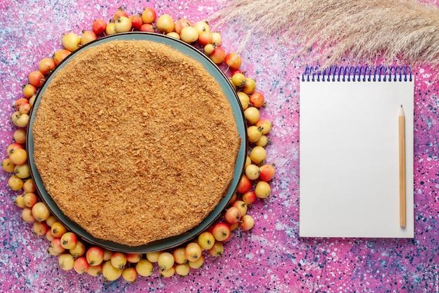 Вид сверху восхитительный круглый торт внутри тарелки с черешней в подкладке и блокнотом на ярко-розовом столе торт пирог бисквит сладкая выпечка сахар Бесплатные Фотографии