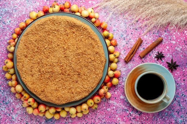 Вид сверху восхитительный круглый торт внутри тарелки с черешней в подкладке и чаем на ярко-розовом бисквитном пироге на столе Бесплатные Фотографии