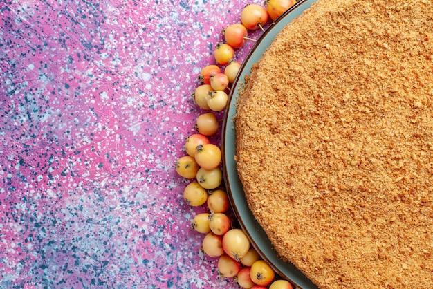 Вид сверху восхитительный круглый торт на тарелке с черешенкой на ярко-розовом столе, пирог, бисквит, сладкая выпечка Бесплатные Фотографии