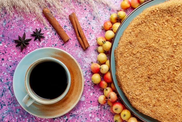 Вид сверху восхитительный круглый торт внутри тарелки с чаем из черешни и корицей на ярко-розовом бисквитном пироге на столе Бесплатные Фотографии
