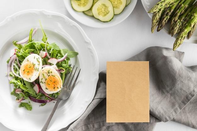 Vista dall'alto deliziosa insalata su un piatto bianco con scheda vuota Foto Gratuite