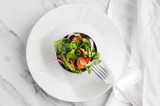 Vista dall'alto deliziosa insalata su un piatto bianco Foto Gratuite
