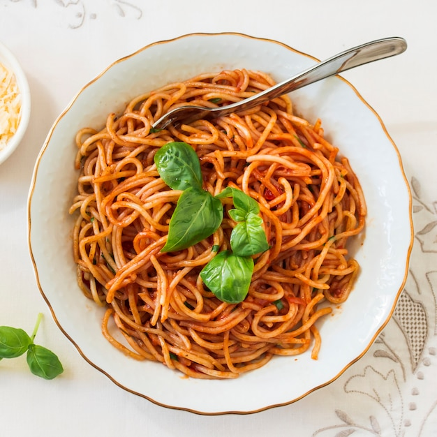 Top view of delicious spaghetti with basil on ceramic plate Free Photo