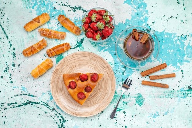 Vista dall'alto della deliziosa torta alle fragole affettata torta gustosa con tè alla cannella e braccialetti su una torta di bacche blu brillante e dolce Foto Gratuite