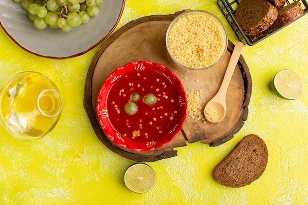黄色いテーブルスープミール野菜料理にパンとおいしいトマトソースの上面図 無料写真