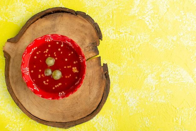 黄色い机の上の緑のブドウとおいしいトマトソースの上面図スープフードミールディナー 無料写真