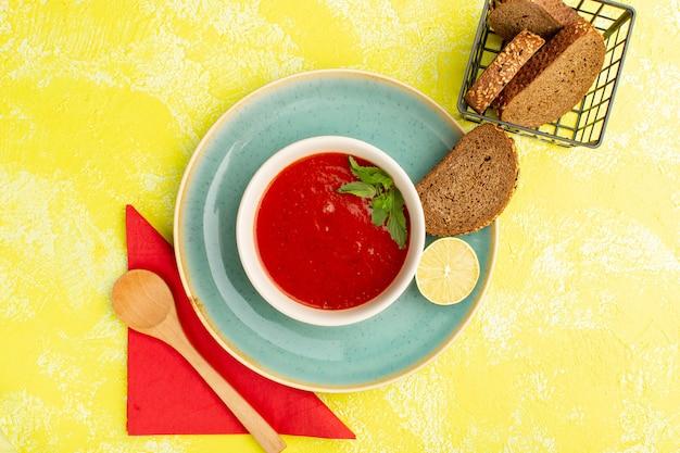 黄色いテーブルの上にパンのパンとスープミールディナー野菜の上面図おいしいトマトスープ 無料写真