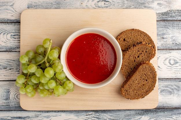 灰色のテーブルに緑のブドウとライ麦パンのトップビューおいしいトマトスープ、スープフードミールディナー 無料写真