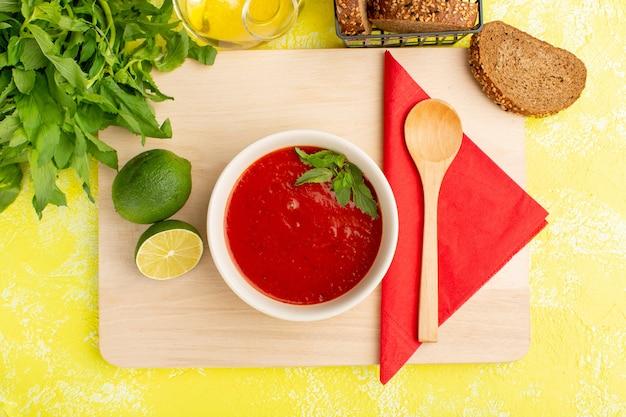 トップビュー黄色のテーブルにレモンとグリーンのおいしいトマトスープ、スープフードミールディナー 無料写真